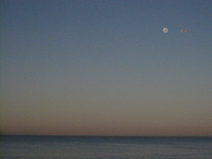 Moon waning in dawn sky, with plane pointing it out