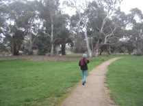 Kaye walking ahead through the park