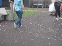 Half a person walking through jacaranda confetti at the market