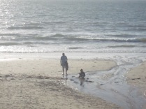 Man and his son (I'd guess) playing at the beach