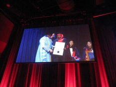Arefa on the screen receiving her certificate from John Hill