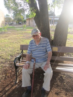 Dad sitting on Rose's bench in the park in Auburn