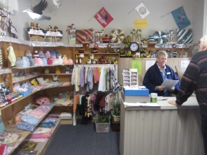 Liz at the counter with a customer and the goods at the front of the shop - beanies, footy gear, knitted gear etc