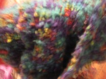 A blurry close up of a rainbow hued scarf knitted by Marian
